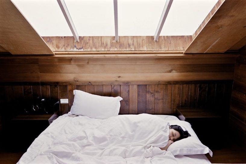 femme lit couverture blanche oreiller
